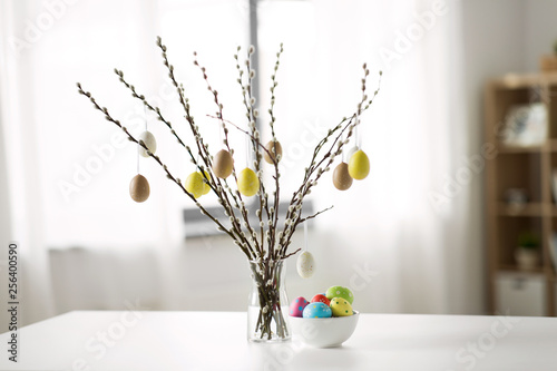 Leinwanddruck Bild holidays and object concept - pussy willow branches decorated by easter eggs in vase on table