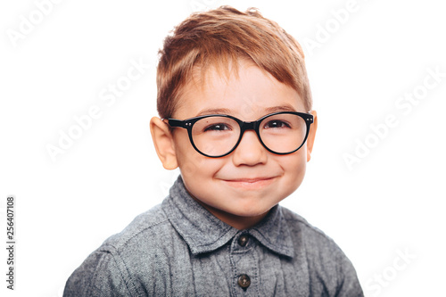 little boy with eyeglasses looking at camera on white background