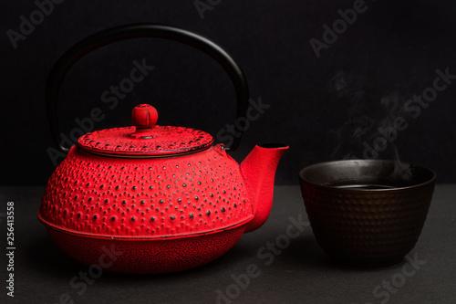 Tetera roja de hierro fundido sobre fondo negro y cuenco con Té © Mercedes Fittipaldi