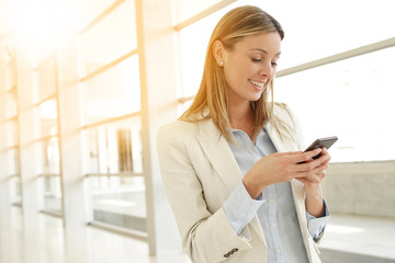 Businesswoman texting in contemporary office