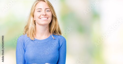 Leinwandbild Motiv Beautiful young woman wearing blue sweater over isolated background Smiling with hands palms together receiving or giving gesture. Hold and protection