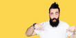 Leinwandbild Motiv Young hipster man with long hair and beard wearing casual white t-shirt Pointing down with fingers showing advertisement, surprised face and open mouth