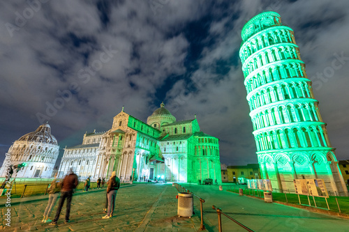 Pisa Tower and Cathedral in Miracles Square for St Patrick's Day illuminated by green lights, Tuscany - Italy