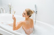 Leinwanddruck Bild - beautiful and smiling woman taking bath and holding champagne glass in bathroom