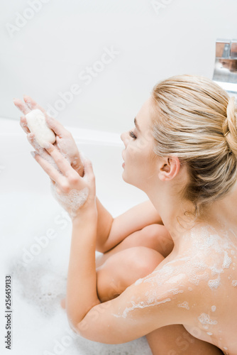 Leinwanddruck Bild attractive and blonde woman taking bath with foam and holding soap in bathroom