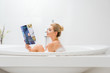 Leinwanddruck Bild - side view of attractive and blonde woman taking bath with foam and reading beauty and style magazine in bathroom