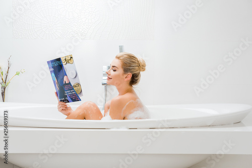 Leinwanddruck Bild side view of attractive and blonde woman taking bath with foam and reading beauty and style magazine in bathroom