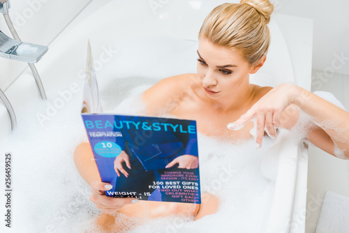 Leinwanddruck Bild selective focus of attractive and blonde woman taking bath with foam and pointing with finger at beauty and style magazine