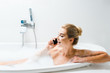 Leinwanddruck Bild - attractive and smiling woman taking bath with foam and talking on smartphone in bathroom