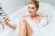 Leinwanddruck Bild - selective focus of attractive and smiling woman taking bath and taking selfie in bathroom