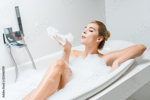Leinwanddruck Bild attractive and blonde woman taking bath and playing with foam in bathroom
