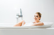 Leinwanddruck Bild - attractive and blonde woman taking bath with foam and looking at camera in bathroom