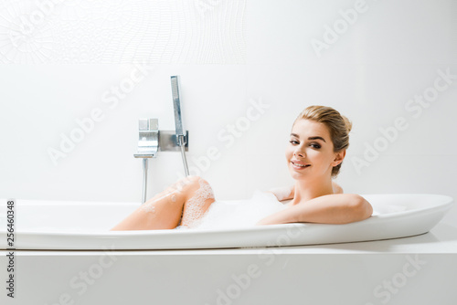 Leinwanddruck Bild attractive and blonde woman taking bath with foam and looking at camera in bathroom