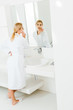 Leinwanddruck Bild - selective focus of beautiful and blonde woman in white bathrobe using cotton pad and looking at mirror