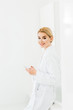 Leinwanddruck Bild - beautiful and smiling woman in white bathrobe with eye patches on face holding smartphone