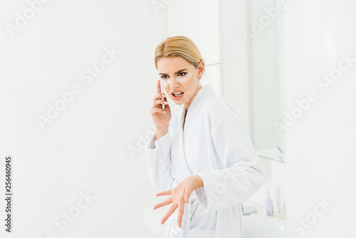 Leinwanddruck Bild beautiful and irritated woman in white bathrobe with eye patches on face talking on smartphone