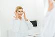 Leinwanddruck Bild - selective focus of beautiful and blonde woman in white bathrobe applying eye patches in bathroom
