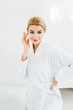 Leinwanddruck Bild - beautiful and blonde woman in white bathrobe with eye patches on face looking at camera in bathroom