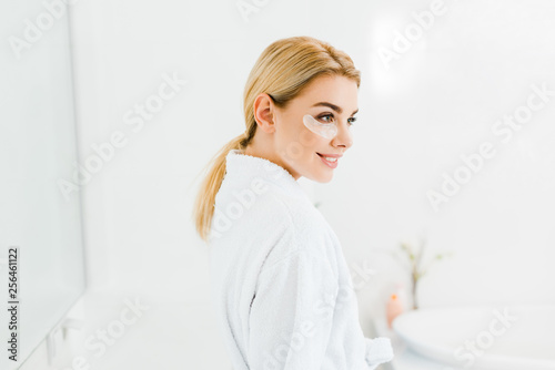 Leinwanddruck Bild beautiful and smiling woman in white bathrobe with eye patches on face looking away in bathroom