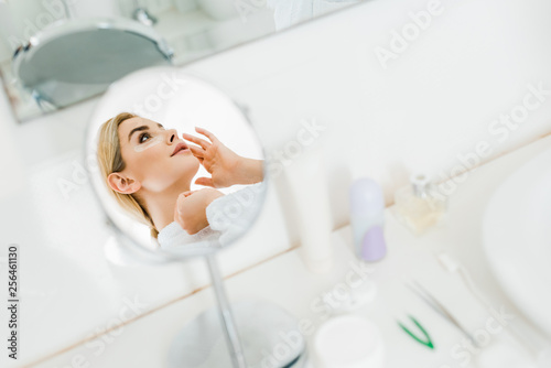 Leinwanddruck Bild selective focus of attractive and blonde woman in white bathrobe applying eye patches in bathroom