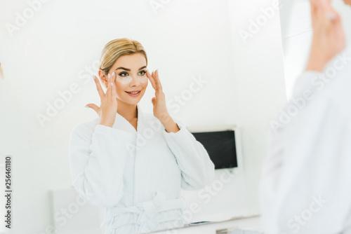 Leinwanddruck Bild selective focus of beautiful and blonde woman in white bathrobe applying eye patches in bathroom