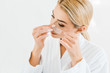 Leinwanddruck Bild - blonde and attractive woman in white bathrobe applying eye patches in bathroom