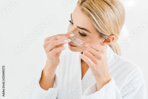 Leinwanddruck Bild blonde and attractive woman in white bathrobe applying eye patches in bathroom