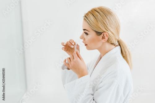 Leinwanddruck Bild beautiful and blonde woman in white bathrobe applying eye patches in bathroom