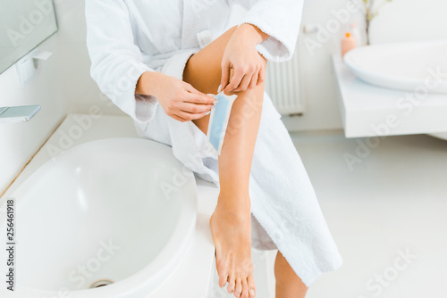 Leinwanddruck Bild cropped view of young adult woman using depilation stripe in bathroom