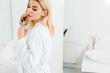 Leinwanddruck Bild - beautiful and blonde woman in white bathrobe using flat iron and looking away in bathroom