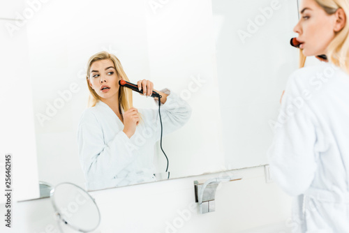 Leinwanddruck Bild selective focus of beautiful and blonde woman in white bathrobe using flat iron