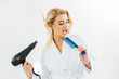 Leinwanddruck Bild - beautiful and smiling woman in white bathrobe singing and holding hairdryer and comb