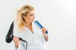 Leinwanddruck Bild - beautiful and smiling woman in white bathrobe holding hairdryer and comb