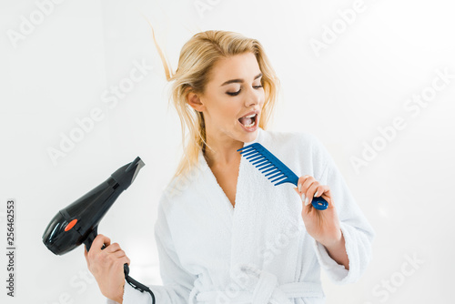 Leinwanddruck Bild beautiful and smiling woman in white bathrobe singing and holding hairdryer and comb