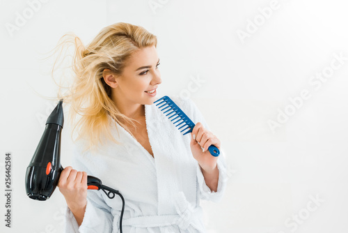 Leinwanddruck Bild beautiful and smiling woman in white bathrobe holding hairdryer and comb