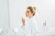 Leinwanddruck Bild - beautiful and smiling woman in bathrobe using perfume and looking at mirror