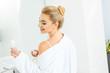 Leinwanddruck Bild - blonde and smiling woman in white bathrobe holding deodorant in bathroom