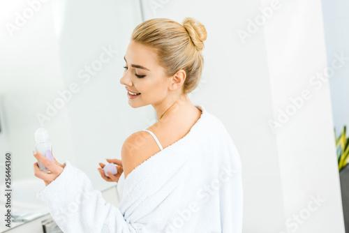 Leinwanddruck Bild blonde and smiling woman in white bathrobe holding deodorant in bathroom