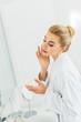 Leinwanddruck Bild - attractive and blonde woman in white bathrobe applying face cream in bathroom