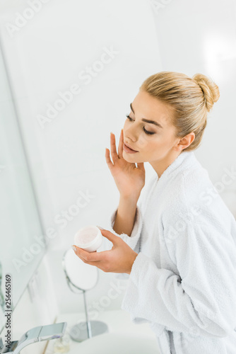 Leinwanddruck Bild attractive and blonde woman in white bathrobe applying face cream in bathroom