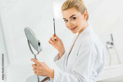 Leinwanddruck Bild attractive woman in white bathrobe holding cosmetic brush and looking at camera