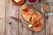 croissant with strawberry jam, fresh strawberries and a coffee on wooden table - 256465598