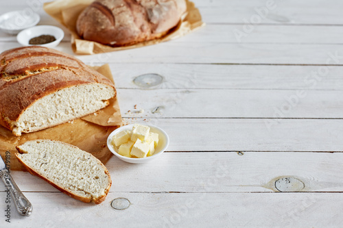 Bread loaf with butter on white background