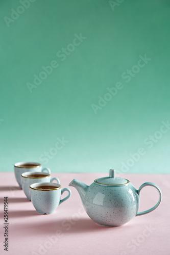 Tea pot with three tea on blue backdrop © Maris Kiselov