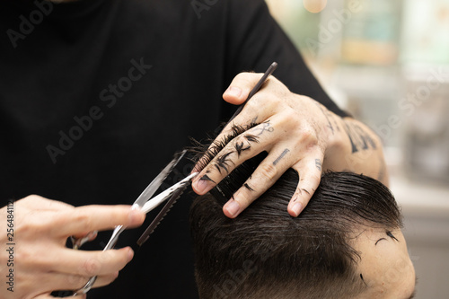 Handsome bearded man, having hair cut by scissors at barber shop .