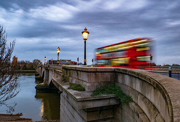 Putney bridge early in the morning at twilight and public transport by traditional red bus in motion in London, UK