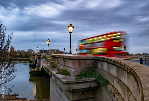 obraz lub plakat Putney bridge early in the morning at twilight and public transport by traditional red bus in motion in London, UK