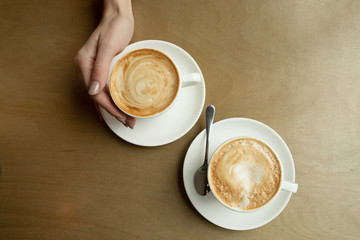 Two cups of cappuccino with latte art in white cups on wooden table. Morning coffee for couple in love. Top view.
