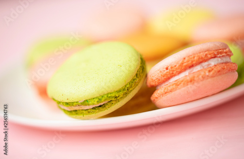 Colorful French or Italian macarons stack on white plate put on pink wood table with copy space for background. Dessert for served with afternoon tea or coffee break.