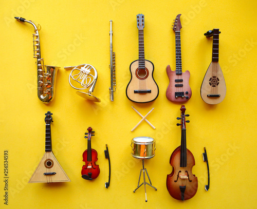 Toy musician instruments on bright yellow background - 256534593